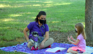 a young girl reads to a small grey Schnauzer and his handler. The girl and handler are wearing masks and the visit is taking placce outside in the shade of a tree where the LAPS team and client can social distance, yet still interact.